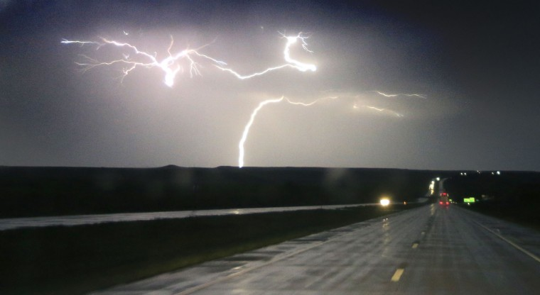 Lightning strikes along Interstate 70 near Junction City, Kan., Tuesday, April 26, 2016. Thunderstorms bearing hail as big as grapefruit and winds approaching hurricane strength lashed portions of the Great Plains on Tuesday. (AP Photo/Orlin Wagner)