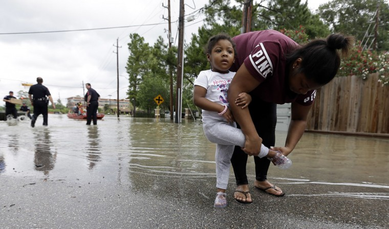 Brittany Parker puts a shoe back on her daughter Zoey after being rescued from their flooded apartment complex, Tuesday, April 19, 2016, in Houston. Storms have dumped more than a foot of rain in the Houston area, flooding dozens of neighborhoods. (AP Photo/David J. Phillip)