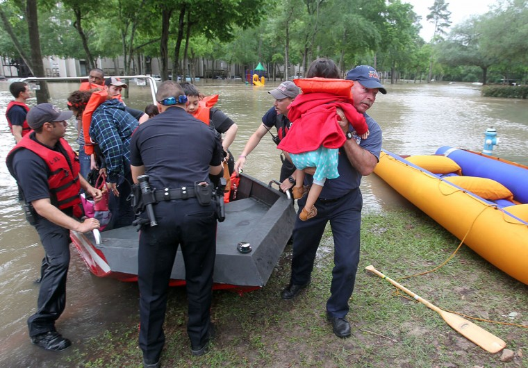 Spring firefighter Kenneth Eisfeldt lifts 3-year-old Valerie Negrete to safety as the family is evacuated from One Westfield Lake Apartment in Houston, Texas, Wednesday, April 20, 2016. The Negrete family had not been out of their home since Sunday. Thousands of people have been evacuated from their homes and major highways were closed after the rains that started Sunday overwhelmed Houston's bayous. Forecasters have issued another flash flood watch for Houston through Wednesday night. (Steve Gonzales/Houston Chronicle via AP)