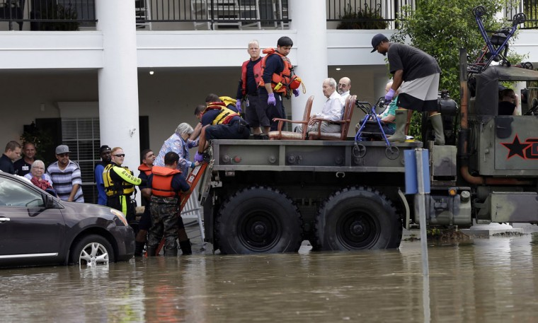 Residents are evacuated from a retirement and assisted living complex as floodwaters rise Tuesday, April 19, 2016, in Spring, Texas. Storms have dumped more than a foot of rain in the Houston area, flooding dozens of neighborhoods. (AP Photo/David J. Phillip)