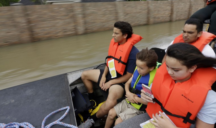 Simon Holden, left, rides in the front of an airboat with his brother Phillip, center, and sister Brianna along with Chris Villarreal, rear right, as they are evacuated from their flooded neighborhood Tuesday, April 19, 2016, in Spring, Texas. Storms have dumped more than a foot of rain in the Houston area, flooding dozens of neighborhoods. (AP Photo/David J. Phillip)