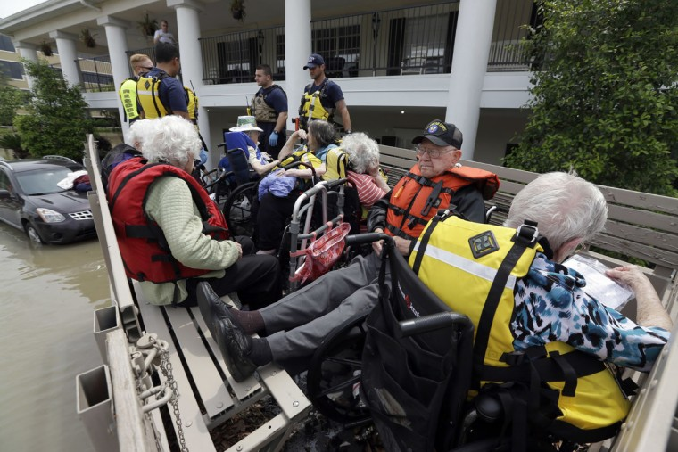 Residents of a retirement and assisted living complex are evacuated as floodwaters rise around the facility, Tuesday, April 19, 2016, in Spring, Texas. Storms have dumped more than a foot of rain in the Houston area, flooding dozens of neighborhoods. (AP Photo/David J. Phillip)