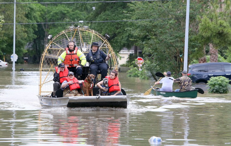People and their pets are rescued from their homes near Nanes at Baltic in Houston, Texas, Wednesday, April 20, 2016.Thousands of people have been evacuated from their homes and major highways were closed after the rains that started Sunday overwhelmed Houston's bayous. Forecasters have issued another flash flood watch for Houston through Wednesday night. (Steve Gonzales/Houston Chronicle via AP)