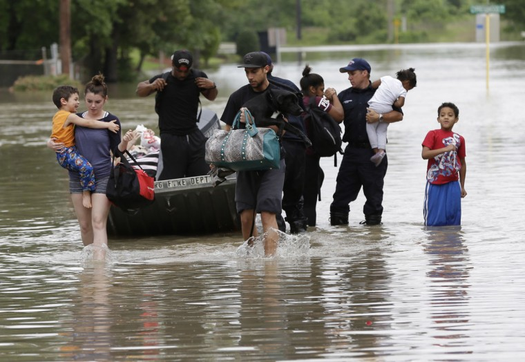 Residents walk through floodwaters after being evacuated from their flooded apartment complex, Tuesday, April 19, 2016, in Houston. Storms have dumped more than a foot of rain in the Houston area, flooding dozens of neighborhoods. (AP Photo/David J. Phillip)