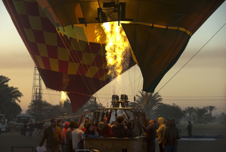 In this picture taken Friday, April 1, 2016, a hot air balloon prepares to take off on the west bank of the Nile River in Luxor, Egypt. They take off at first light, providing sky-high views of antiquities below. Luxor in southern Egypt is one of the world's largest outdoor museums, with majestic temples and tombs of ancient kings. (AP Photo/Amr Nabil)