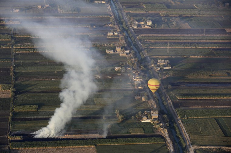In this picture taken from a balloon Friday, April 1, 2016, smoke rises as farmers burn chaff after a harvest on the west bank of the Nile River in Luxor, Egypt. The details of life in rural Egypt come into view as the balloon begins its descent, with farmers toiling in the fields and children heading to school. The path of the brightly colored balloons is determined by prevailing winds. (AP Photo/Amr Nabil)