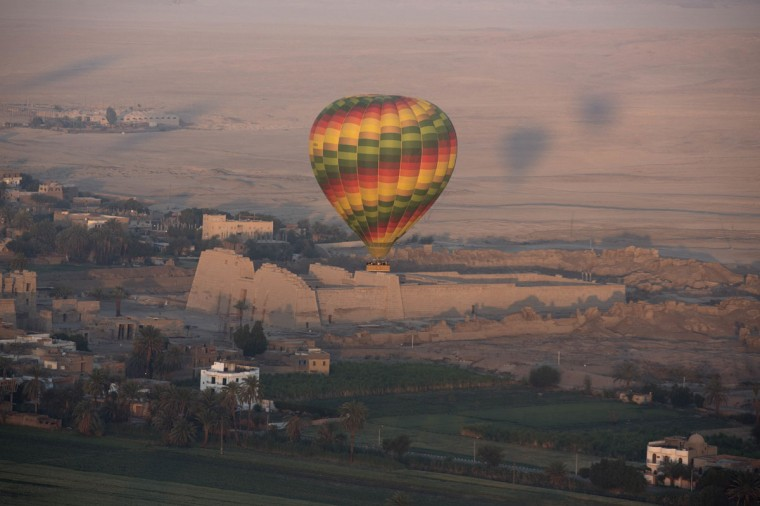 In this picture taken from a balloon Friday, April 1, 2016, a hot air balloon flies over the mortuary temple of Ramsis III at Medinet Habu on the west bank of the Nile River in Luxor, Egypt. Only from a balloon high in the sky, in the clear air of the early morning, can a visitor begin to grasp the beauty of antiquities on the ground in this one-time Egyptian capital once known as Thebes. (AP Photo/Amr Nabil)