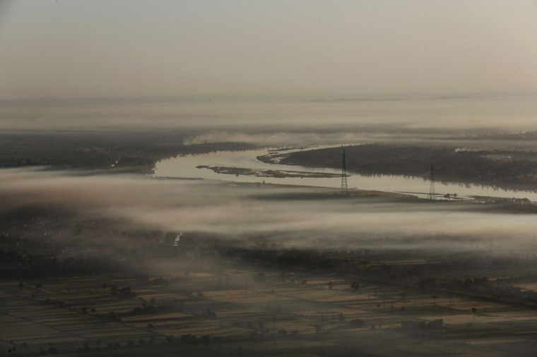 In this picture taken from a balloon Friday, April 1, 2016, the Nile River is partially shrouded in early morning clouds in Luxor, Egypt. They take off at first light, balloons over Luxor, Egypt, providing sky-high views of antiquities below. The city in southern Egypt is one of the world's largest outdoor museums, with majestic temples and tombs of ancient kings. (AP Photo/Amr Nabil)