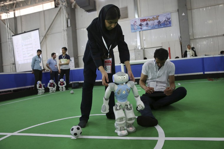Iranian participants of the international robotics competition RoboCup Iran Open 2016, prepare their humanoid robot prior to a soccer match, in Tehran, Iran, Wednesday, April 6, 2016. (AP Photo/Vahid Salemi)