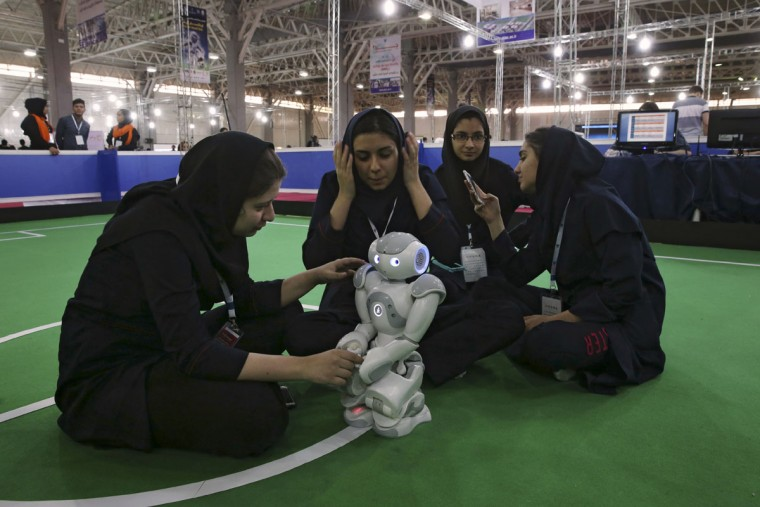 Iranian schoolgirls members of GraceBand team prepare their humanoid robot prior to a soccer match with Dainamite team from Germany during the international robotics competition, RoboCup Iran Open 2016, in Tehran, Iran, Wednesday, April 6, 2016. The event, organized by Iranian RoboCup Regional Committee and Qazvin Azad University, was participated by 320 teams from Iran and abroad. The 3-day competitions kicked off on Wednesday at Tehran's Permanent Fairground. (AP Photo/Vahid Salemi)