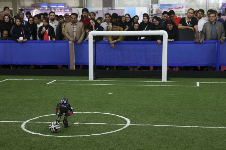 A humanoid robot plays in a soccer match while visitors follow the competition during the international robotics competition, RoboCup Iran Open 2016, in Tehran, Iran, Wednesday, April 6, 2016. The event, organized by Iranian RoboCup Regional Committee and Qazvin Azad University, was participated by 320 teams from Iran and abroad. The 3-day competitions kicked off on Wednesday at Tehran's Permanent Fairground. (AP Photo/Vahid Salemi)