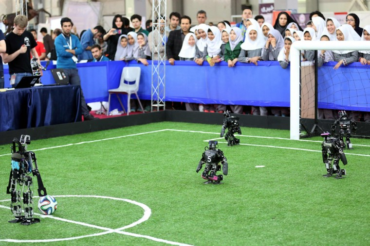 Robots from German FUmanoids team, of Berlin United University, and from Bit Bots team, of Hamburg University, take part in a soccer match during the RoboCup Iran Open 2016, in Tehran, on April 6, 2016. (ATTA KENARE/AFP/Getty Images)