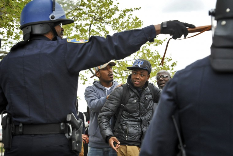 A Baltimore police officer directs people as rioting breaks out near Mondawmin Mall after the April 27, 2015, funeral for Freddie Gray. Gray was arrested at Gilmor Homes on April 12, 2015, and suffered injuries while in police custody that later proved fatal. He died April 19. (Amy Davis/Baltimore Sun)