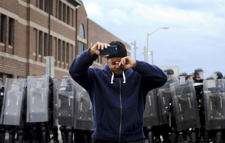Rashad Riddick, 36, wipes his eyes as he takes pictures of the police line at at North and Pennsylvania avenues, near the CVS Pharmacy that was looted and set afire. Crowds filled the streets in several parts of the city on the day of Freddie Gray's funeral. Gray died April 19, 2015, from injuries sustained while in police custody. (Algerina Perna/Baltimore Sun)