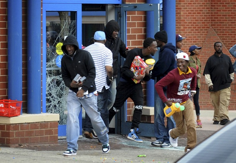Looters carry a variety of merchandize as they leave the CVS store April 27, 2015, at Pennsylvania and North avenues during the rioting. Stores in other areas were looted and vandalized as well. (Jerry Jackson/Baltimore Sun)