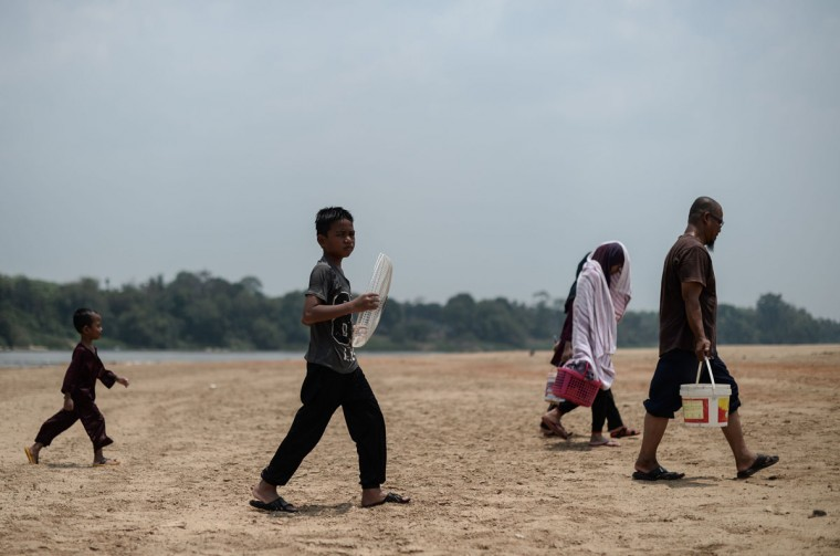 Villagers walk along the dry banks of the Pahang river as schools remain closed due to the ongoing heatwave in Termerloh, outside Kuala Lumpur, on April 11, 2016. (MOHD RASFAN/AFP/Getty Images)