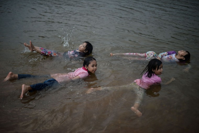 Children play in a river to cool off as schools remain closed due to the ongoing heatwave in Temerloh, outside Kuala Lumpur, on April 11, 2016. (MOHD RASFAN/AFP/Getty Images)