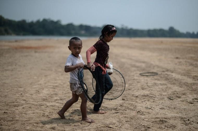 Children walk along the dry banks of the Pahang river as schools remain closed due to the ongoing heatwave in Temerloh, outside Kuala Lumpur, on April 11, 2016. (MOHD RASFAN/AFP/Getty Images)
