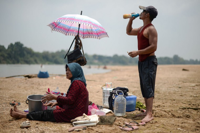 A man drinks water along the dry banks of the Pahang river as schools remain closed due to the ongoing heatwave in Termerloh, outside Kuala Lumpur, on April 11, 2016. (MOHD RASFAN/AFP/Getty Images)