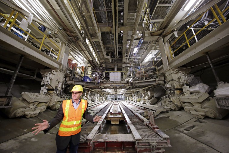 A television reporter stands in view of the backside of the boring machine known as Bertha inside the State Route 99 tunnel that is under construction during a tour for media members Monday, April 25, 2016, in Seattle. The Alaskan Way viaduct, which the two-mile tunnel will replace, is scheduled to be closed for about two weeks beginning Friday, April 29, as a precaution as tunnel boring begins under the structure. The tunneling machine is boring a double-decker traffic tunnel to replace the viaduct damaged in an earthquake in 2001. (AP Photo/Elaine Thompson)