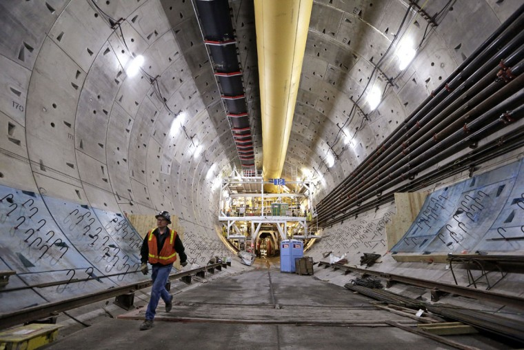 A worker walks inside the State Route 99 tunnel that is under construction Monday, April 25, 2016, in Seattle. The Alaskan Way viaduct, which the two-mile tunnel will replace, is scheduled to be closed for about two weeks beginning Friday, April 29, as a precaution as tunnel boring begins under the structure. The tunneling machine is boring a double-decker traffic tunnel to replace the viaduct damaged in an earthquake in 2001. (AP Photo/Elaine Thompson)