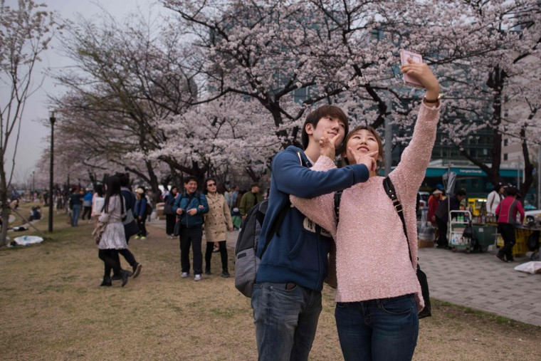 In a photo taken on April 6, 2016 a couple take a selfie beneath cherry blossoms on Yeouido island in Seoul. The annual cherry blossom festival on Yeouido island in central Seoul runs from April 1-10. (ED JONES/AFP/Getty Images)