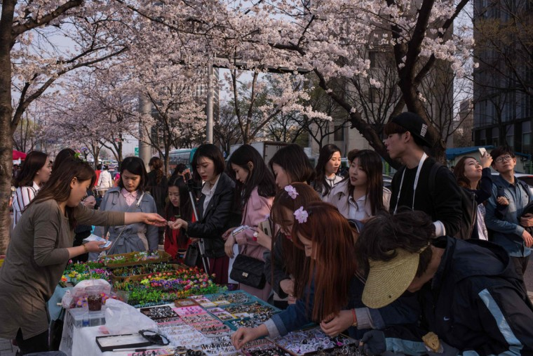 In a photo taken on April 6, 2016 people browse a stall beneath cherry blossoms on Yeouido island in Seoul. The annual cherry blossom festival on Yeouido island in central Seoul runs from April 1-10. (ED JONES/AFP/Getty Images)