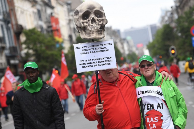 "A demonstrator holds a placard reading ""This is the future of our social insurance"", during a national anti-austerity protest on May 24, 2016, in Brussels. Belgian trade unions called for mass protests against the centre-right government's proposed work reforms as they plan rallies and strikes over the next few months. / (Dirk Waem/AFP/Getty Images)"
