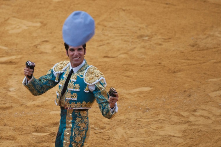 A spectator throws a hat to Spanish matador Cayetano Rivera as he holds up his two bull's ears trophy during the Corpus bullfighting festival at the bullring of Granada on May 25, 2016. (JORGE GUERRERO/AFP/Getty Images)