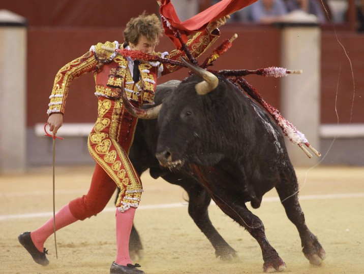 "Spanish matador Roman performs a pass with ""muleta"" to a bull during the San Isidro Feria at Las Ventas bullring in Madrid on May 19, 2016. (Alberto Simon/AFP/Getty Images)"