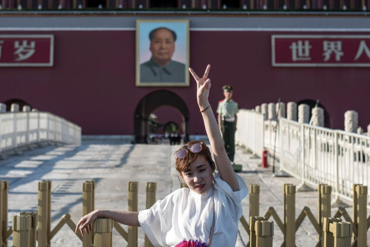 A tourist poses in front of a giant portrait of Mao Zedong at the gate of the Forbidden City in Beijing on May 16, 2016. Official Chinese media stayed largely silent about Monday's 50th anniversary of the start of the bloody Cultural Revolution, with discussion of the tumultuous decade still controlled on the mainland. (AFP PHOTO / FRED DUFOUR)