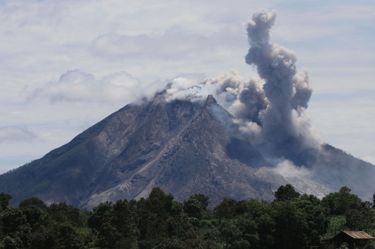 The Sinabung volcano spews hot clouds of ash, as seen from the Simpang Empat subdistrict in Karo, North Sumatra on May 22, 2016. The death toll from a volcanic eruption in western Indonesia has climbed to six, an official said on May 22, with fears more could have been trapped by the hot ash. (AFP PHOTO / ARDIANSYAH PUTRA)