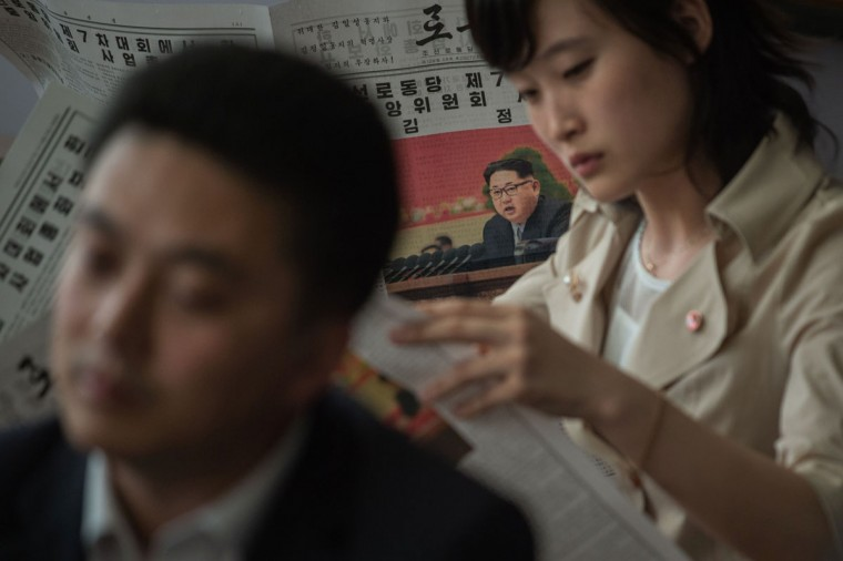 "North Korean guides read newspapers showing coverage of North Korean leader Kim Jong-Un delivering a speech at the 7th Workers Party Congress, in the lobby of the Yanggakdo hotel in Pyongyang on May 8, 2016. North Korean leader Kim Jong-Un told a rare ruling party congress that his country was a ""responsible"" nuclear weapons state, with a no first-use policy and a commitment to non-proliferation, state media reported on May 8. (AFP PHOTO / Ed Jones)"