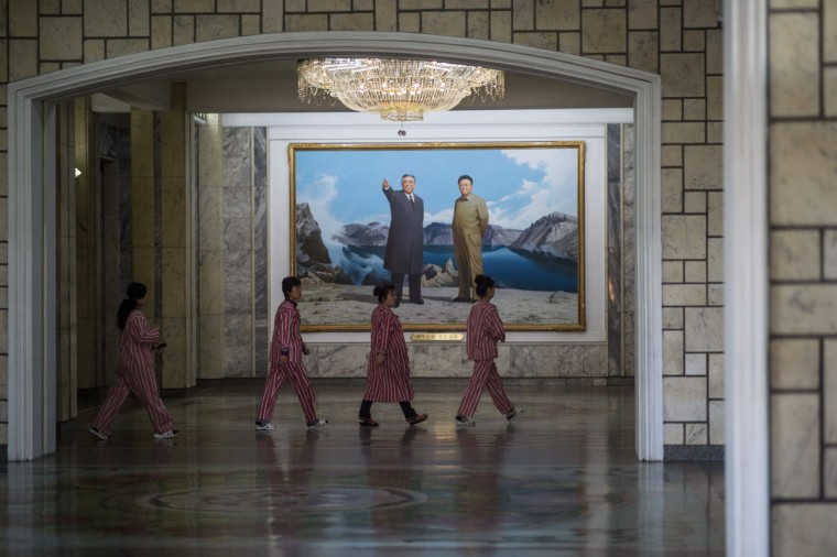 Patients walk thorugh a hallway past a portrait of late North Korean leader Kim Il-Sung (L) and Kim Jong-Il (R) at the Pyongyang Maternity Hospital during a government-organised media tour in Pyongyang on May 7, 2016. North Korea organised an unusual media tour of a gleaming modern hospital, apparently seeking to highlight its leaders' love for the people during a major ruling party gathering. The Pyongyang Maternity Hospital owes everything to the party and to the Kim dynasty which has ruled the country since its creation, according to officials who escorted foreign reporters around the showpiece institution. (AFP PHOTO / Ed Jones)