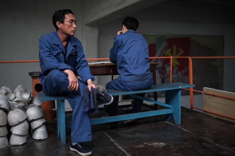 Workers sit on a bench during a media tour of the March 26 Electric Cable Factory in Pyongyang on May 6, 2016. When one of the world's most secretive states opens the door to the international media, it keeps a firm grip on the handle. Some 130 journalists flocked to North Korea at the express invitation of the Pyongyang authorities to cover the opening of a rare ruling party congress. They got within 200 meters of the venue, the April 25 Palace, and that was where they were stopped -- on the other side of the road, under a steady drizzle that had been falling on the capital all morning. Instead of a rare glimpse of the country's highest-level political meeting for almost four decades, the media were then offered a tour of the March 26 Electric Cable Factory. North Korea issues reporting visas sparingly and escorts all journalists to make sure it sets the agenda and gets its point across. (AFP PHOTO / Ed Jones)