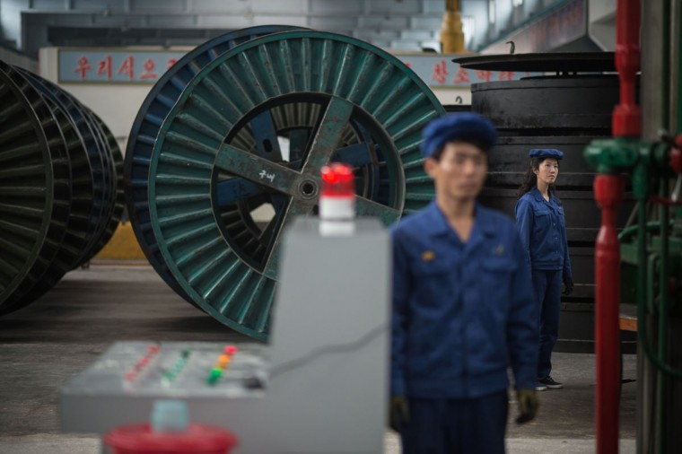 A worker stands before machinery during a media tour of the March 26 Electric Cable Factory in Pyongyang on May 6, 2016. When one of the world's most secretive states opens the door to the international media, it keeps a firm grip on the handle. Some 130 journalists flocked to North Korea at the express invitation of the Pyongyang authorities to cover the opening of a rare ruling party congress. They got within 200 meters of the venue, the April 25 Palace, and that was where they were stopped -- on the other side of the road, under a steady drizzle that had been falling on the capital all morning. Instead of a rare glimpse of the country's highest-level political meeting for almost four decades, the media were then offered a tour of the March 26 Electric Cable Factory. North Korea issues reporting visas sparingly and escorts all journalists to make sure it sets the agenda and gets its point across. (AFP PHOTO / Ed Jones ED JONES/AFP/Getty Images)