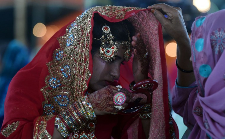 A Pakistani bride adjusts a jhoomar as she attenda a mass-wedding ceremony in Karachi on late May 9, 2016. (ASIF HASSAN/AFP/Getty Images)