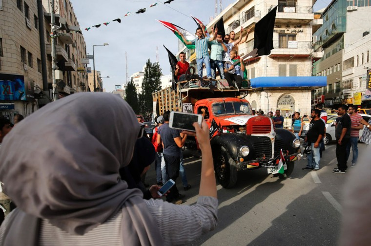 "Palestinian refugees stand on a classic truck as they take part in a rally to commemorate the 68th anniversary of the ""Nakba"" in the West Bank city of Ramallah on May 15, 2016. ""Nakba"" means in Arabic ""catastrophe"" in reference to the birth of the state of Israel 68-years-ago in British-mandate Palestine, which led to the displacement of hundreds of thousands of Palestinians who either fled or were driven out of their homes during the 1948 war over Israel's creation. The key symbolises the homes left by Palestinians in 1948. (AFP PHOTO / ABBAS MOMANIA)"