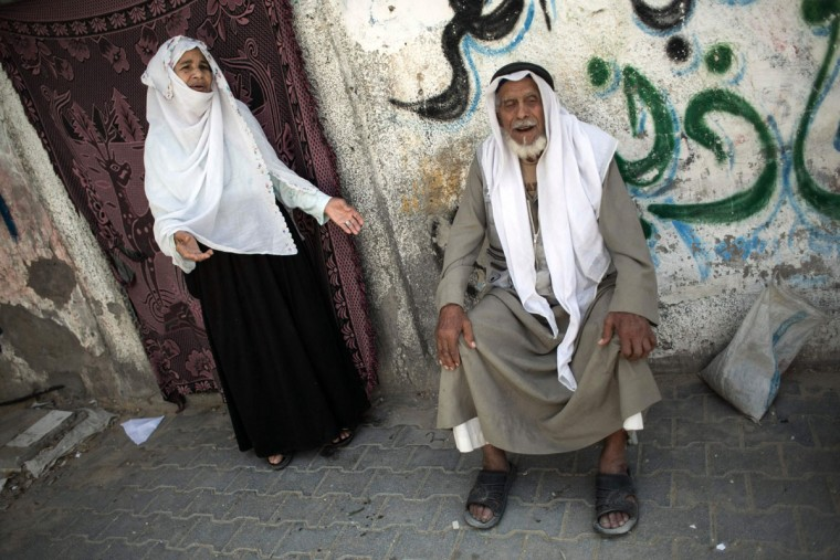 "Palestinian refugee Ibrahim Abu Mustaf (R), 83, who says is a former inhabitant of the town of Beersheva, sits next to his wife Amna, 75, outside his home in the Khan Yunis refugee camp in the southern Gaza Strip on May 15, 2016, on the 68th anniversary of the ""Nakba"". ""Nakba"" means in Arabic ""catastrophe"" in reference to the birth of the state of Israel 68-years-ago in British-mandate Palestine, which led to the displacement of hundreds of thousands of Palestinians who either fled or were driven out of their homes during the 1948 war over Israel's creation. The key symbolises the homes left by Palestinians in 1948. (AFP PHOTO / SAID KHATIB)"