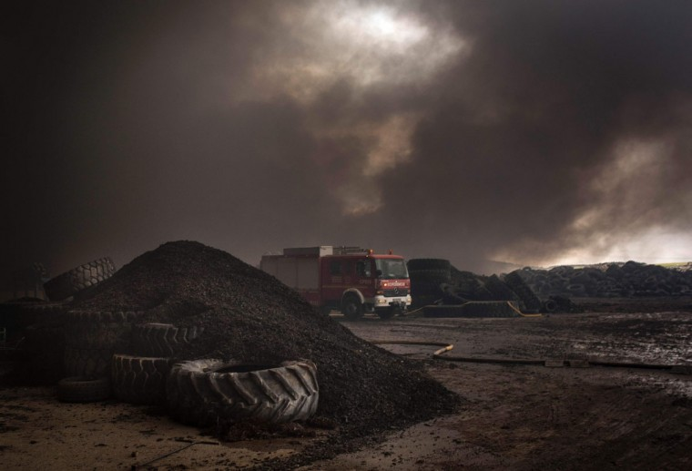 Clouds of dark smoke cover the sky as a fire truck drives among piles of tyres in an uncontrolled dump near the town of Sesena, after a fire brokeout early on May 13, 2016. A huge waste ground near Madrid where millions of tyres have been dumped was on fire today, releasing a thick black cloud of toxic fumes that officials worry could harm residents nearby. (AFP Photo/Pedro Armestre)