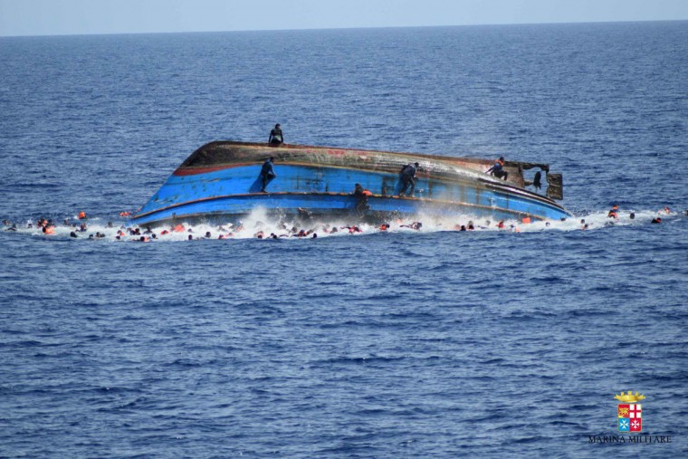 "This handout picture released on May 25, 2016 by the Italian Navy (Marina Militare) shows the shipwreck of an overcrowded boat of migrants off the Libyan coast today. At least seven migrants have drowned after the heavily overcrowded boat they were sailing on overturned, the Italian navy said. The navy said 500 people had been pulled to safety and seven bodies recovered, but rescue operations were continuing and the death toll could rise. The navy's Bettica patrol boat spotted ""a boat in precarious conditions off the coast of Libya with numerous migrants aboard,"" it said in a statement. (AFP PHOTO / MARINA MILITARE)"