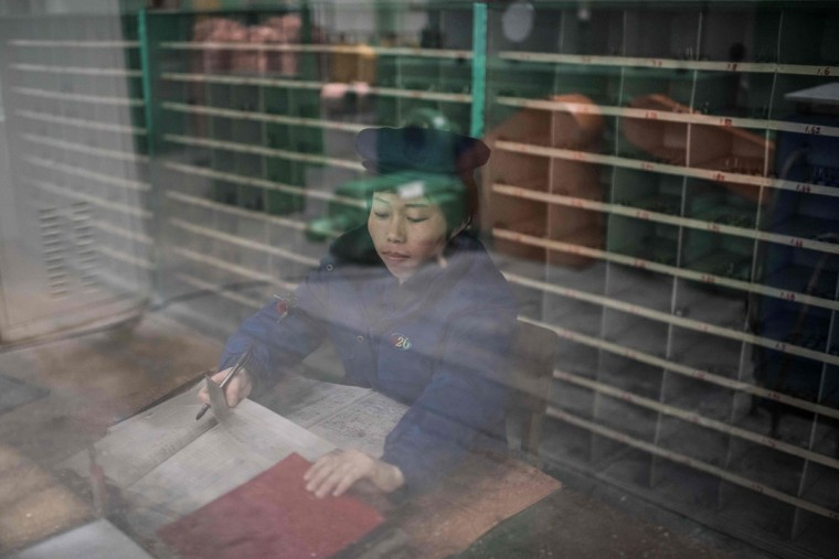 A worker sort documents during a media tour of the March 26 Electric Cable Factory in Pyongyang on May 6, 2016. When one of the world's most secretive states opens the door to the international media, it keeps a firm grip on the handle. Some 130 journalists flocked to North Korea at the express invitation of the Pyongyang authorities to cover the opening of a rare ruling party congress. They got within 200 meters of the venue, the April 25 Palace, and that was where they were stopped -- on the other side of the road, under a steady drizzle that had been falling on the capital all morning. Instead of a rare glimpse of the country's highest-level political meeting for almost four decades, the media were then offered a tour of the March 26 Electric Cable Factory. North Korea issues reporting visas sparingly and escorts all journalists to make sure it sets the agenda and gets its point across. (AFP PHOTO / Ed Jones)