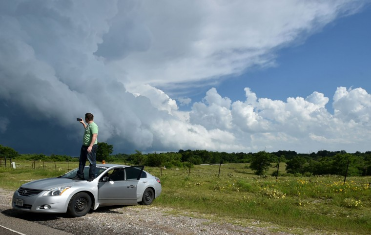 A storm chaser stands on his vehicle while a rain-wrapped tornado wreaks havoc near Hickory, Oklahoma on May 9, 2016. (Josh Edelson/AFP/Getty Images)