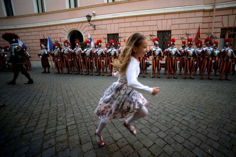 A little girl runs infront of the new swiss guard prior to a swearing-in ceremony in Vatican City, on May 6, 2016. The annual swearing in ceremony for the new papal Swiss guards takes place on May 6, commemorating the 147 who died defending Pope Clement VII on the same day in 1527 during the sack of Rome. (AFP Photo/Filippo Monteforte)