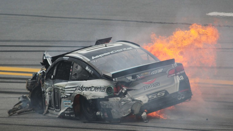 Flames trail Danica Patrick's car after she crashed into Matt Kenseth during the NASCAR Talladega auto race at Talladega Superspeedway, Sunday, May 1, 2016, in Talladega, Ala. (AP Photo/Greg McWilliams)