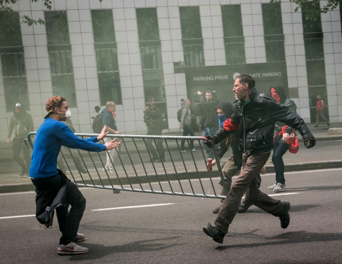 Protestors run with a barricade during a trade union protest in Brussels on Tuesday, May 24, 2016. Tens of thousands of demonstrators marched through the center of the capital to protest the center-right government's social and economic policies which trade unions say cuts deep into the foundations of Belgium's welfare state. (AP Photo/Aurore Belot)