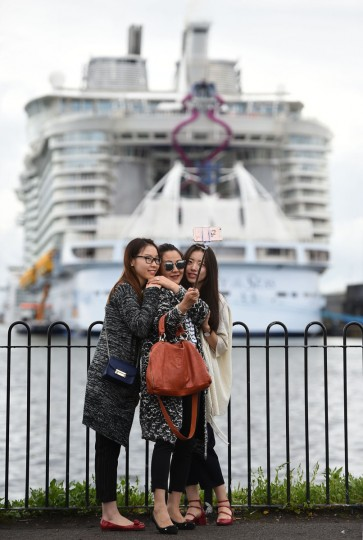 Women take a selfie before the world's largest passenger ship, MS Harmony of the Seas, owned by Royal Caribbean, as it waits to leave Southampton, England, Sunday, May 22, 2016. (Andrew Matthews/PA via AP)