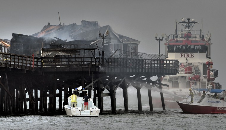 Firefighters work to put out a fire on the Seal Beach pier in Seal Beach, Calif. on Friday, May 20, 2016. The blaze erupted early Friday at the end of the long wooden pier southeast of Los Angeles. Smoke was pouring out of holes in the roof, much of which had collapsed. The restaurant has been closed since 2013. (Jeff Gritchen/The Orange County Register via AP)