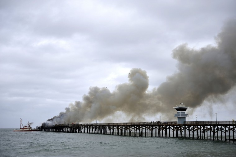 Firefighters work to put out a fire at the end of the Seal Beach Pier in Seal Beach, Calif. on Friday, May 20, 2016. The blaze erupted early Friday at the end of the long wooden pier southeast of Los Angeles. Smoke was pouring out of holes in the roof, much of which had collapsed. The restaurant has been closed since 2013. (Jeff Gritchen/The Orange County Register via AP)