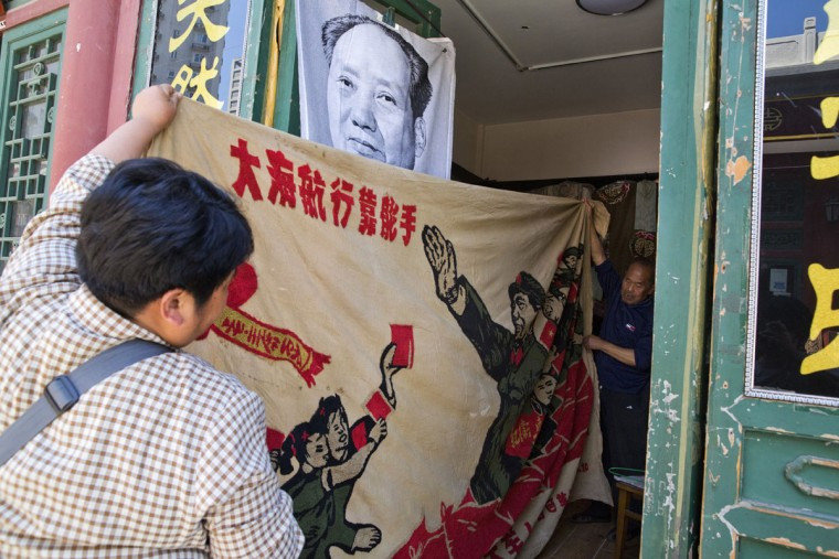 "Vendors unfurl a banner from 1969 depicting former Chinese leader Mao Zedong as he ""inspects the great army of the Cultural Revolution"" and the slogan ""Navigating the seas depends on the helmsman"" at a curio market in Beijing, China, Monday, May 16, 2016. Exactly 50 years ago, China embarked on what was formally known as the Great Proletarian Cultural Revolution, a decade of tumult launched by Mao Zedong to revive communist goals and enforce a radical egalitarianism. The milestone was largely ignored Monday in the Chinese media, reflecting continuing sensitivities about a period that was later declared a ""catastrophe."" (AP Photo/Ng Han Guan)"
